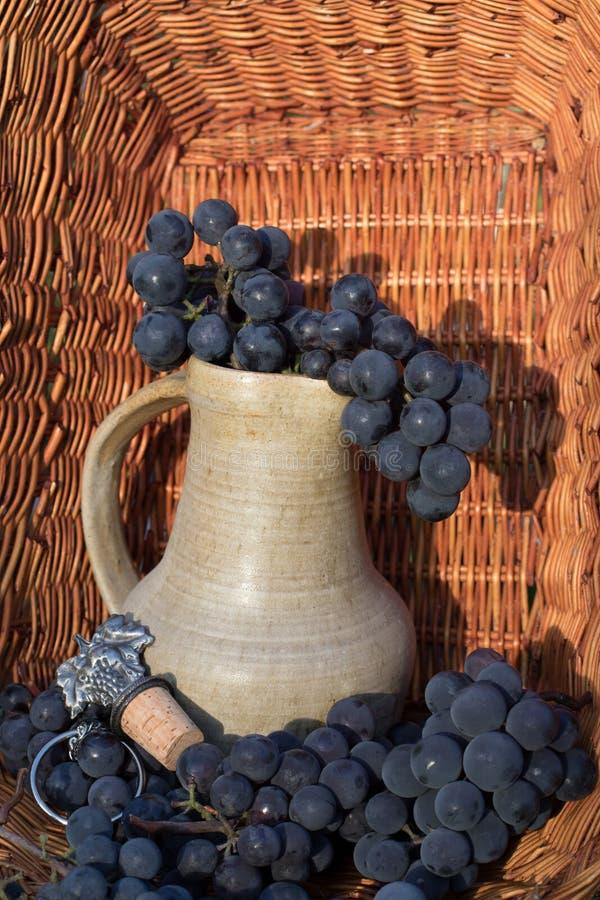 Jarro velho do vinho da argila cercado por grupos da uva e pelo emblema pretos do winemaking imagem de stock royalty free