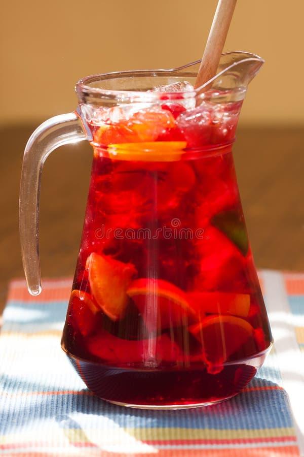 Jarro vermelho bonito da sangria Bebida alcoólica refrigerando com vinho, laranjas e gelo Jarro de vidro em um fundo do guardanap imagem de stock