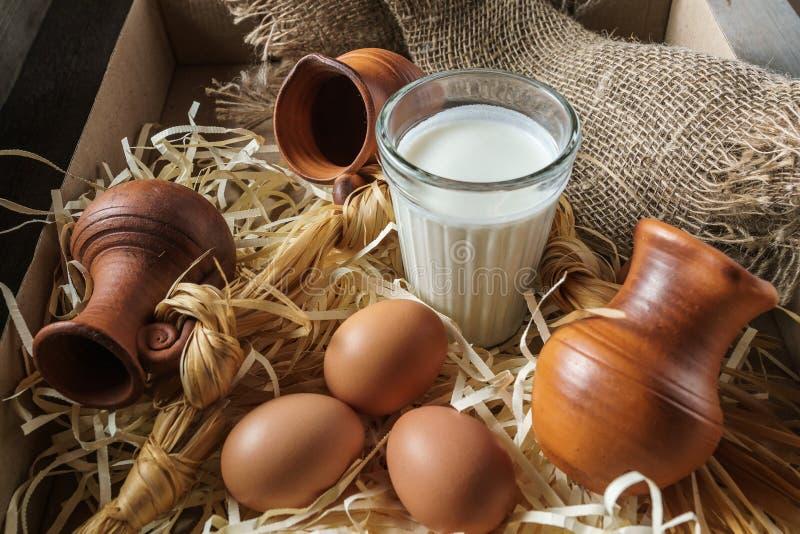 Jarros da argila, ovos, vidro do leite, na palha e em uma serapilheira fotos de stock