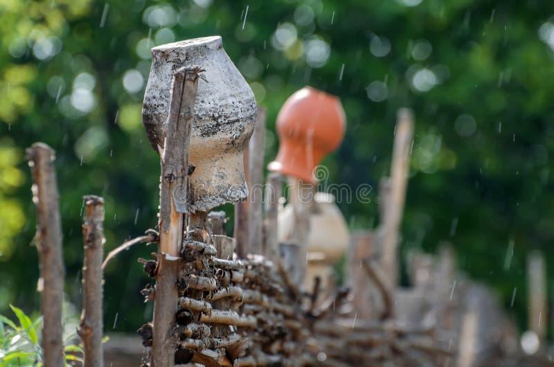 Jarros en la cerca en la lluvia foto de archivo libre de regalías