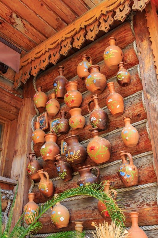 Jarros feitos a mão da argila na parede do log de uma casa da vila fotografia de stock royalty free