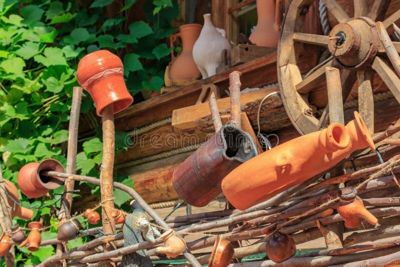 Jarros feitos a mão velhos da argila nos cargos de uma cerca trançada contra a parede de uma casa da vila no dia ensolarado fotos de stock
