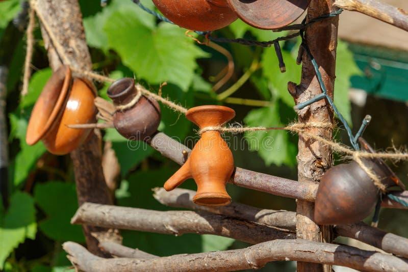 Jarros pequenos feitos a mão da argila que penduram em uma corda na cerca trançada fotografia de stock