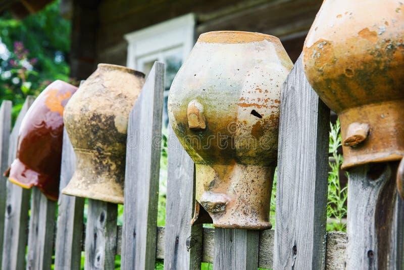 Jarros quebrados velhos da argila na cerca de madeira foto de stock