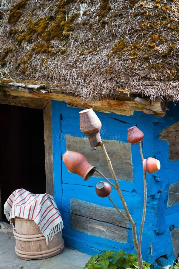 Jarros tradicionais da argila que penduram na frente da porta da casa de madeira velha com telhado cobrido com sapê, cuba da mass foto de stock