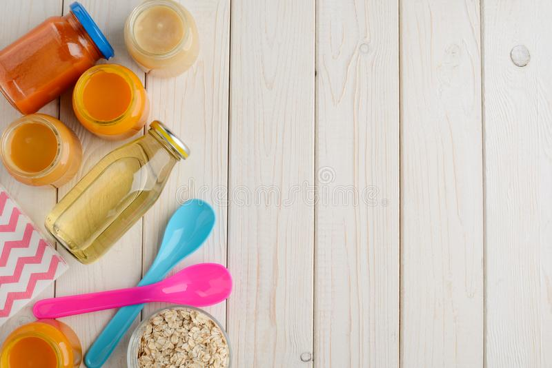 Jars of baby food. Bottle of juice, oat cereal and colorful spoons on wooden background with copy space. Children`s nutrition stock image