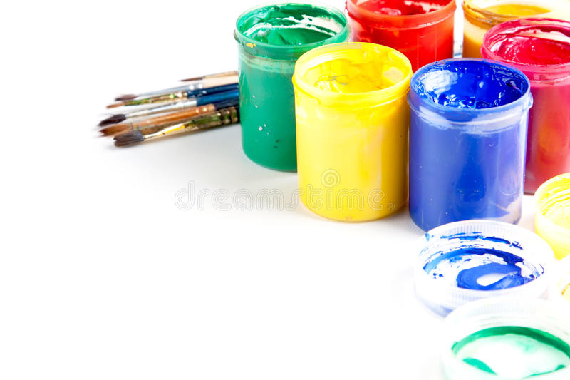 Jars of brightly coloured paint with brushes. Jars of brightly coloured gouache paint with artists brushes and copyspace on a white background royalty free stock photos