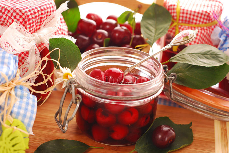 Jars of cherry compote. Jars of homemade cherry compote and basket with fresh fruits stock images