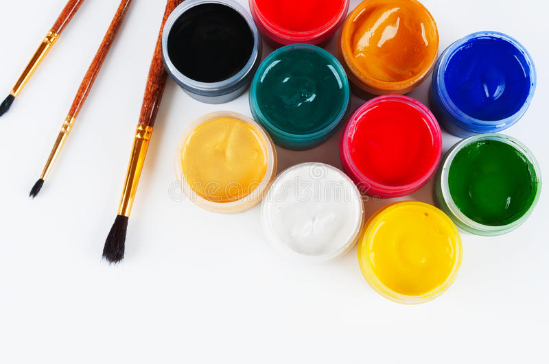Jars with colored gouache and paint brushes. royalty free stock photo
