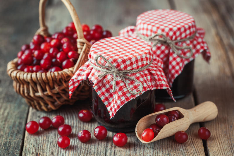 Jars of cranberries jam and basket with bog berry. On background royalty free stock image