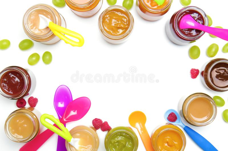 Jars with different baby food and spoons royalty free stock image