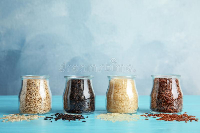 Jars with different types of rice. On blue table stock image