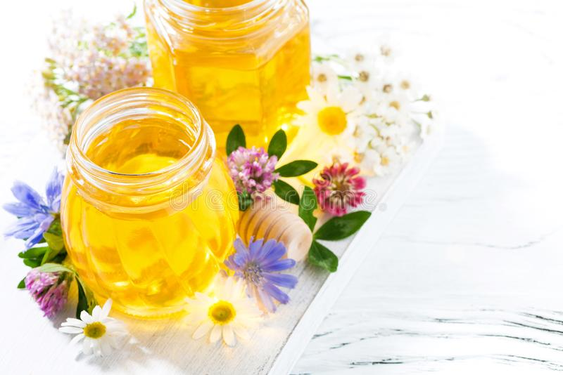 Jars with flower honey on white wooden background, top view closeup. Jars with flower honey on white wooden background, closeup stock photography