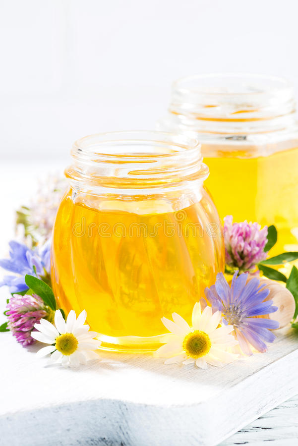 jars with fresh flower honey on white background, vertical royalty free stock images