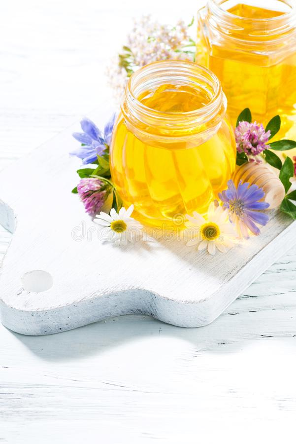 jars with fresh flower honey on white wooden board, vertical royalty free stock image