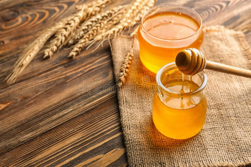 Jars with fresh honey on wooden table stock photo