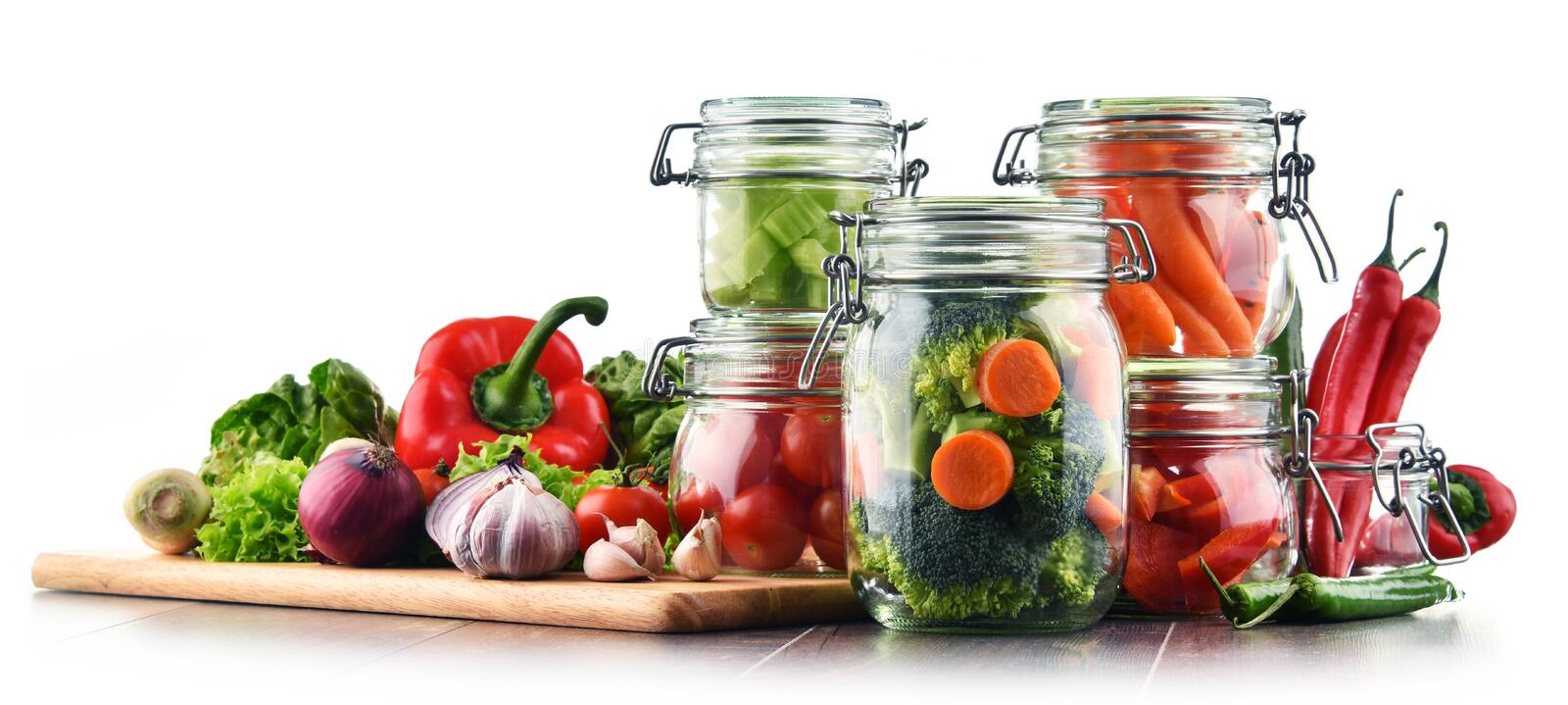 Jars with marinated food and raw vegetables isolated on white.  stock photography