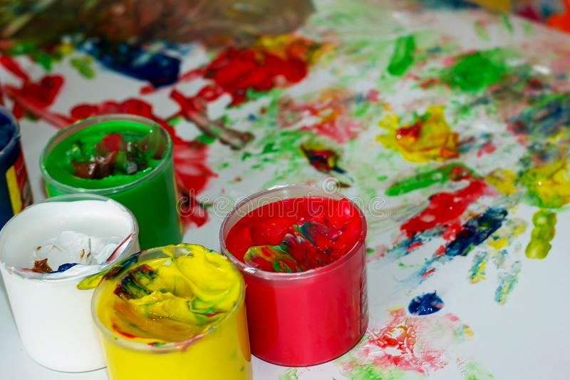 Jars with multi-colored finger paints on the background of children`s prints and blots of paint royalty free stock image