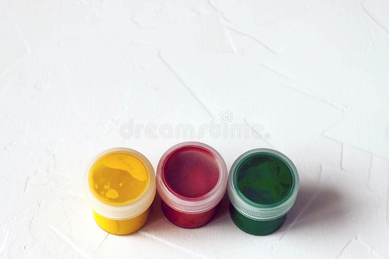 Jars with multi-colored gouache or acrylic paints on a light white background. Selective soft fokus. Text copy space stock images