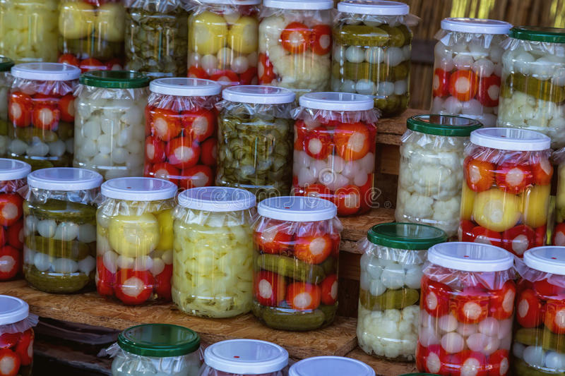 Jars with pickles, cayenne pepper, onions, cucumber and chillies.  royalty free stock photos