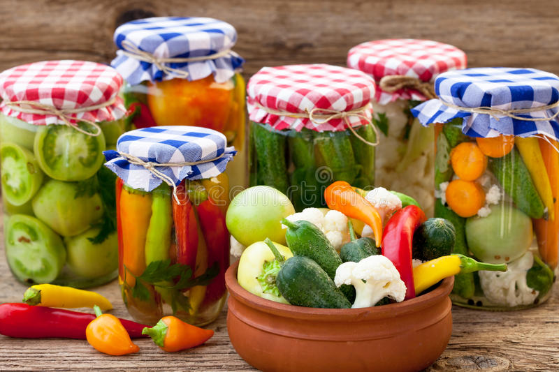 Jars with pickles, tomatoes and chillies royalty free stock photos