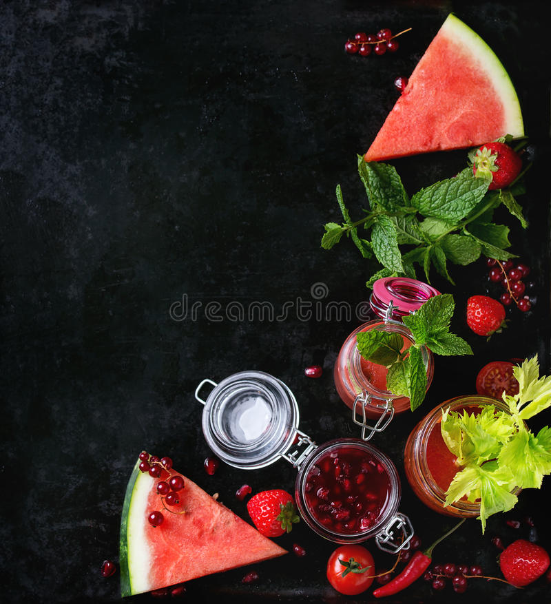 Jars of red smoothies. Variety of red smoothies tomato, strawberry and pomegranate in glass jars, serves with mint, stalk of celery and fresh fruits and stock photos