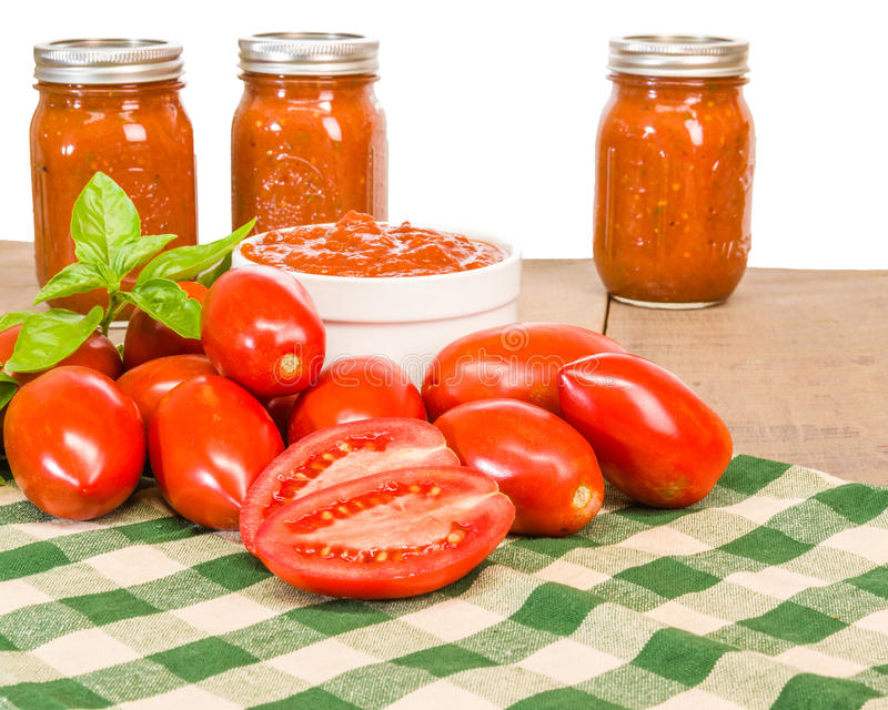Jars of sauce with paste tomatoes and basil royalty free stock photo