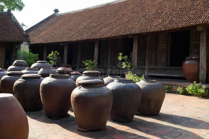 Jars of Tuong in ancient house yard, a kind of fermented bean paste made from soybean and commonly used in Vietnamese cuisine.  stock photo