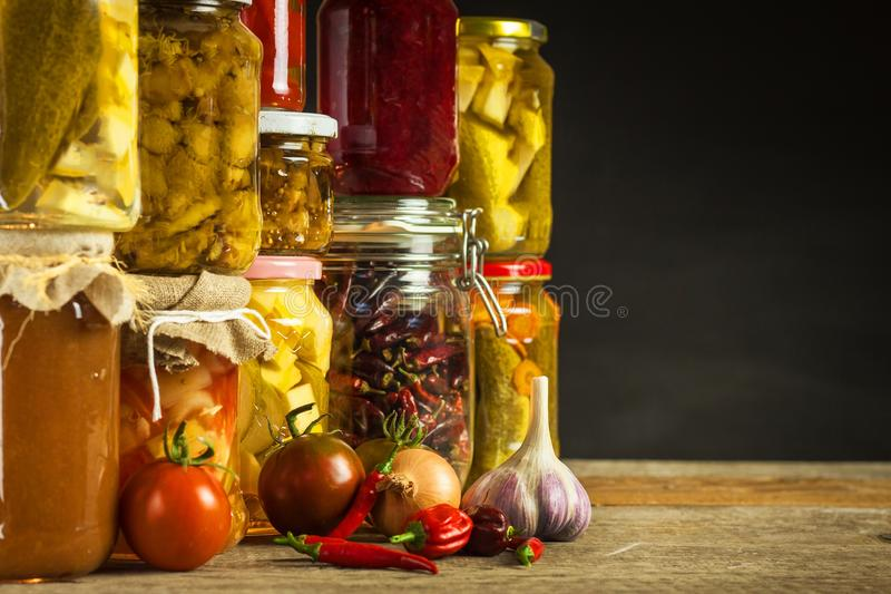 Jars with variety of pickled vegetables. Carrots, field garlic, parsley in glas. Preserved food. Fermented preserved vegetarian fo royalty free stock photos