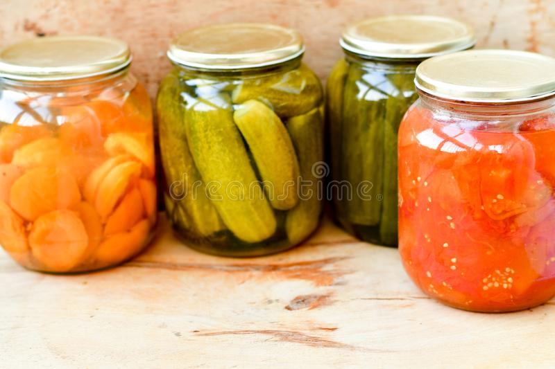 Jars with variety of pickled vegetables. Jars with variety of pickled vegetables and fruits. Preserved food. Home made bio organic pickled cucumber in a jar stock images