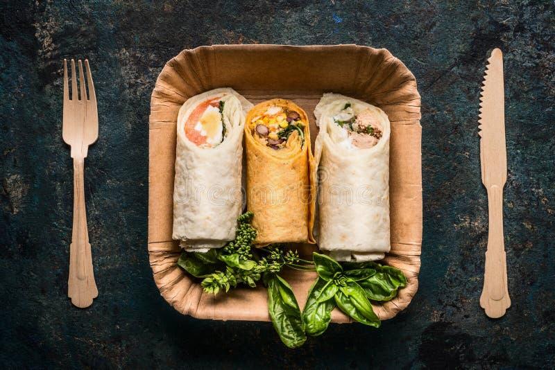Jarscy tortilla opakunki w papierowym talerzu i drewnianym cutlery na ciemnym tle, odgórny widok, zakończenie up Zdrowa lunch prz zdjęcie royalty free