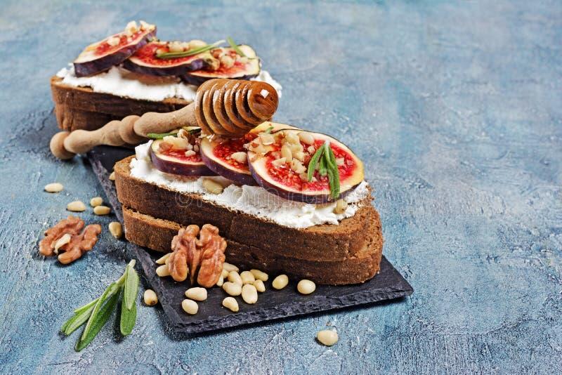 Jarska kanapka z figami, miękki ser, miód, dokrętka i rozmaryny na czerń łupku, wsiadamy fotografia royalty free