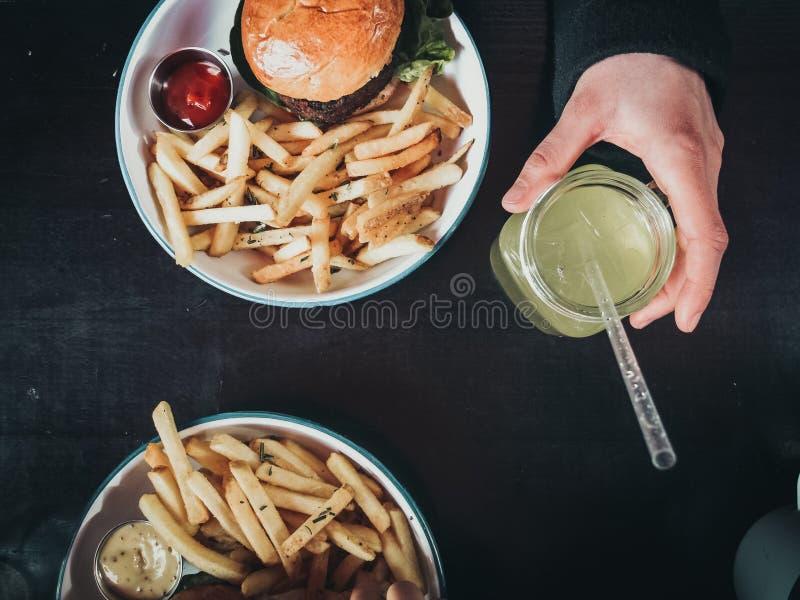Jarski smakowity hamburger, lemoniada i wyśmienicie dłoniaki obrazy stock
