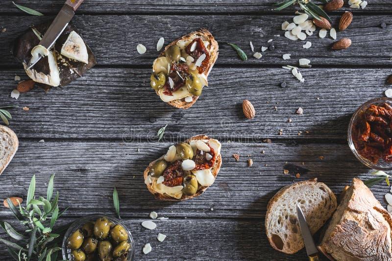 Jarskich migdałów Chlebowi Tapas z Wysuszonymi pomidorami, Zieloną oliwką, serem i migdałami dla śniadanio-lunch, fotografia stock