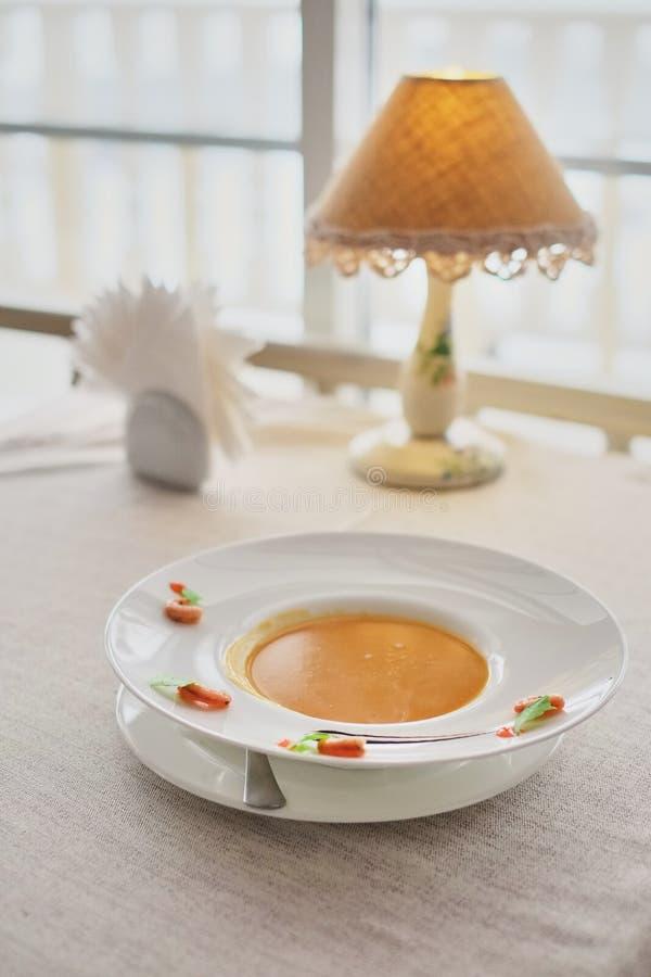Jarzynowa kremowa polewka z marchewką w białym pucharze Odgórny widok na szorstkim białym płótnie cząsteczkowa kuchnia zdjęcie royalty free