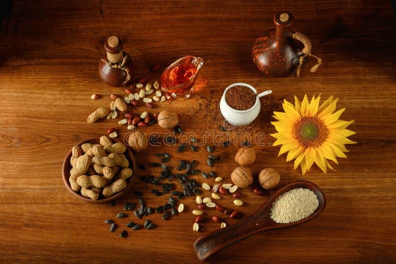 Jarzynowy olej w butelkach, zdrowych ziarnach i dokrętkach, obrazy stock