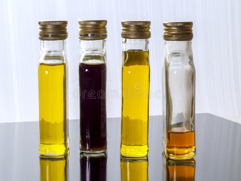 Jarzynowy olej w szklanych przejrzystych butelkach z śrubowymi nakrętkami fotografia stock