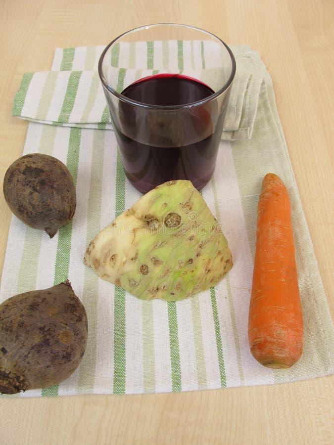 Jarzynowy sok z beetroot, marchewkami i selerowym korzeniem, obrazy stock