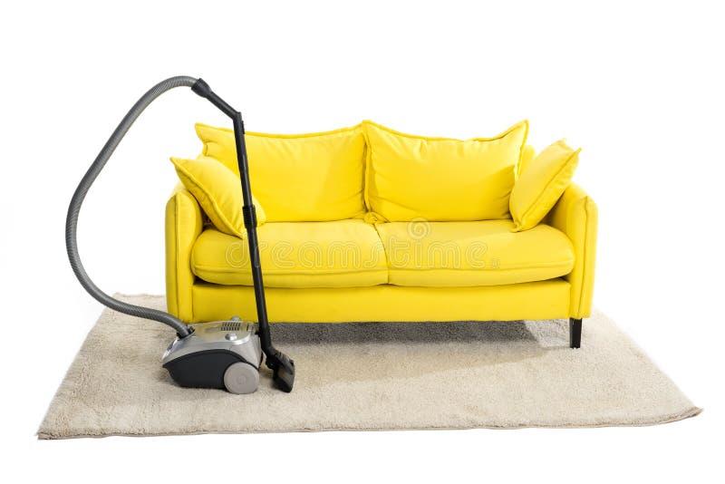 jaskrawa żółta kanapa i próżniowy czysty na dywanie zdjęcie stock