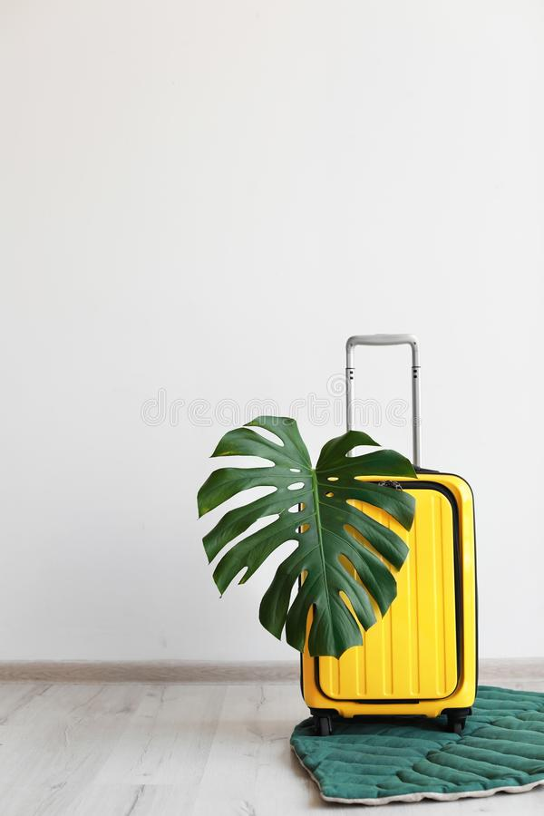 Jaskrawa żółta walizka z tropikalnym liściem fotografia stock