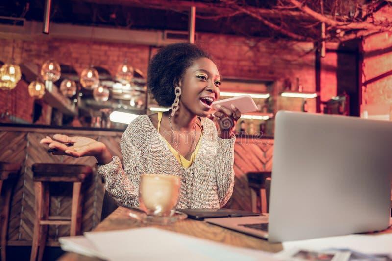Jaskrawa amerykanin kobieta ma biznesową rozmowę telefoniczną w restauracji fotografia stock