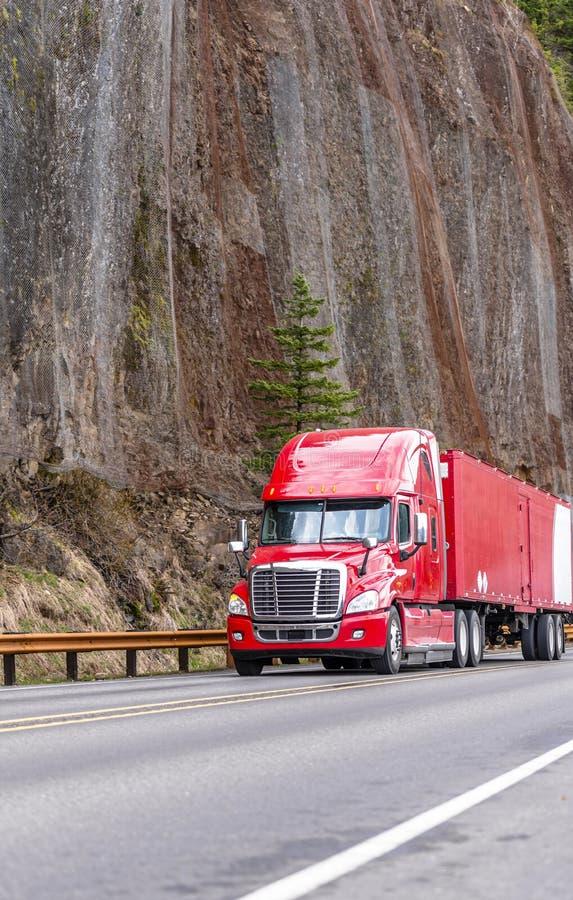 Jaskrawa czerwona duża takielunku semi semi ciężarówka z przyczepa bieg na wijącej halnej drodze z wysoką falezą na stronie zdjęcia stock