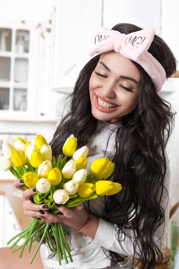 Jaskrawa dziewczyna z uśmiechem w kuchni z а żółtymi tulipanami w kuchni zdjęcie royalty free