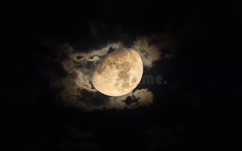 Jaskrawa księżyc otaczająca silky chmurami przy nocą zdjęcia stock