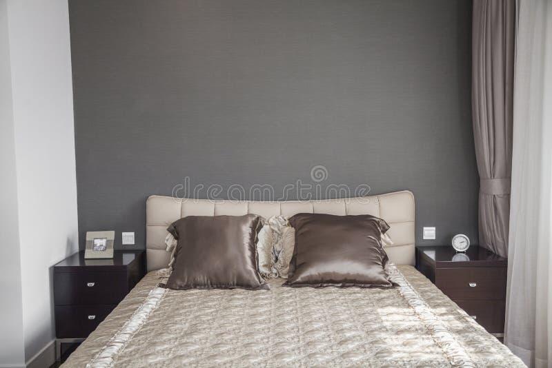 Jaskrawa, nowożytna sypialnia z beżowym bedspread. zdjęcia stock