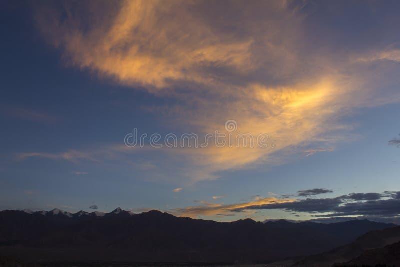 Jaskrawa pomarańcze chmurnieje w wieczór niebie nad pasmem górskim z śnieżnymi szczytami obraz royalty free