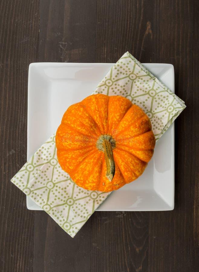 Jaskrawa Pomarańczowa bania siedzi na kwadrat pielusze i talerzu obraz royalty free