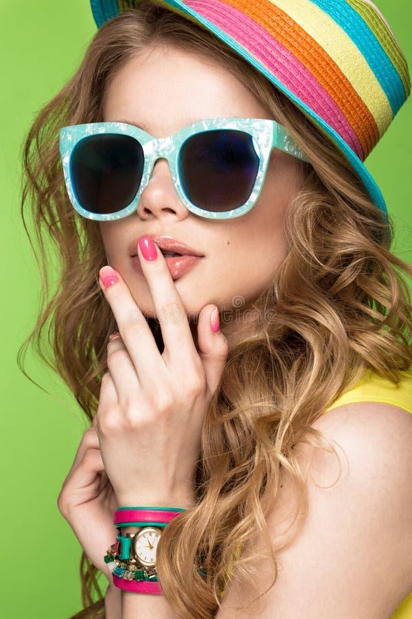 Jaskrawa rozochocona dziewczyna w lato kapeluszu, kolorowy makijaż, kędziory i menchie, robimy manikiur Piękno Twarz fotografia stock