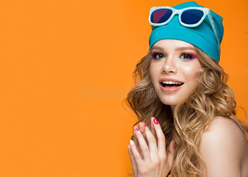 Jaskrawa rozochocona dziewczyna w sporta kapeluszu, kolorowy makijaż, kędziory i menchie, robimy manikiur Piękno Twarz fotografia stock