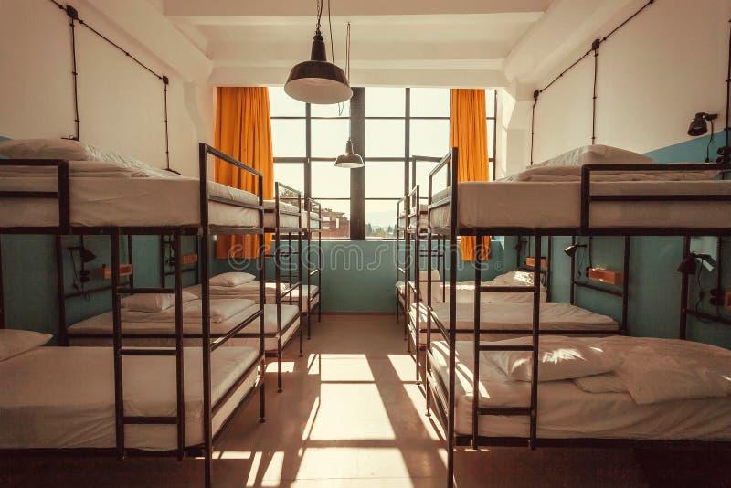 Jaskrawa sypialnia wśrodku schroniska z czystymi koj łóżkami dla uczni i młodzi ludzie obraz royalty free
